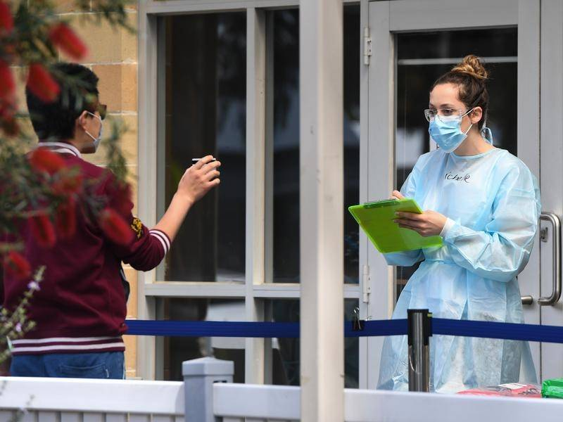 A man shows identification before being tested in Heidelberg West, Melbourne.
